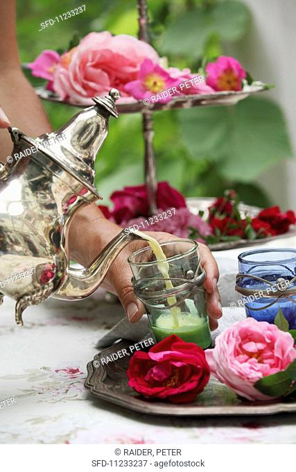 A rose-flavoured sleeping draught being poured into a tea glass decorated with silver
