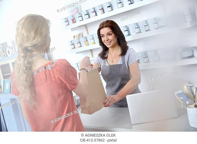 Female business owner giving shopping bag to shopper in art paint shop