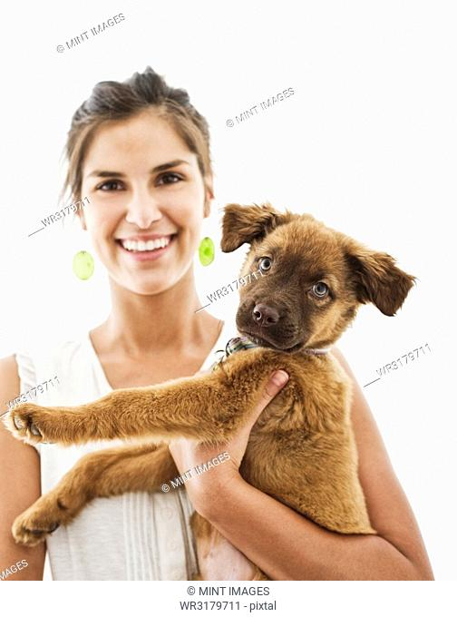Portrait of Hispanic woman at home with her mixed breed puppy