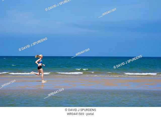 A jogger running along a sand spit in the ocean