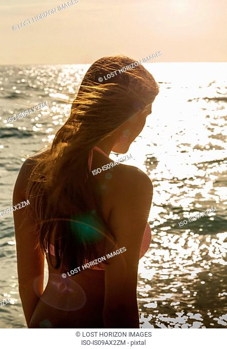 Silhouetted sunlit rear view of young woman at Miami beach, Florida, USA
