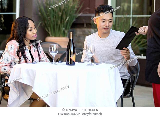 Interracial couple on a date paying for a restaurant tab with a waitress. They are in an outdoor cafe handling the payment bill and server tip or gratuity