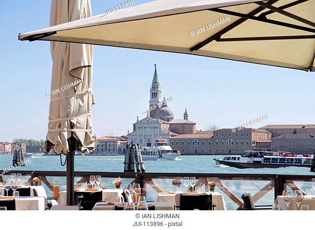 View of San Giorgio Maggiore architecture beyond sunny Grand Canal patio restaurant in Venice, Italy