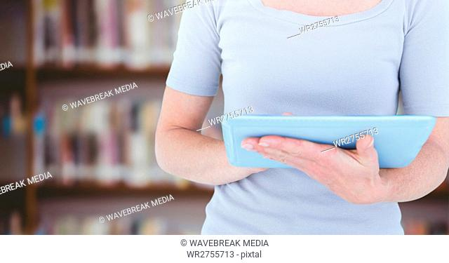 Womans hands on tablet in Library
