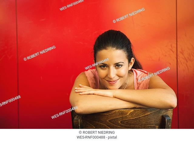 Germany, Munich, Young woman in cafe, smiling, portrait