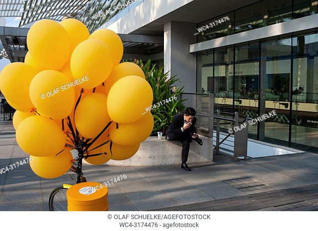 28. 07. 2018, Singapore, Republic of Singapore, Asia - A man in a suit is seen taking a cigarette break in front of the Marina Bay Sands shopping mall