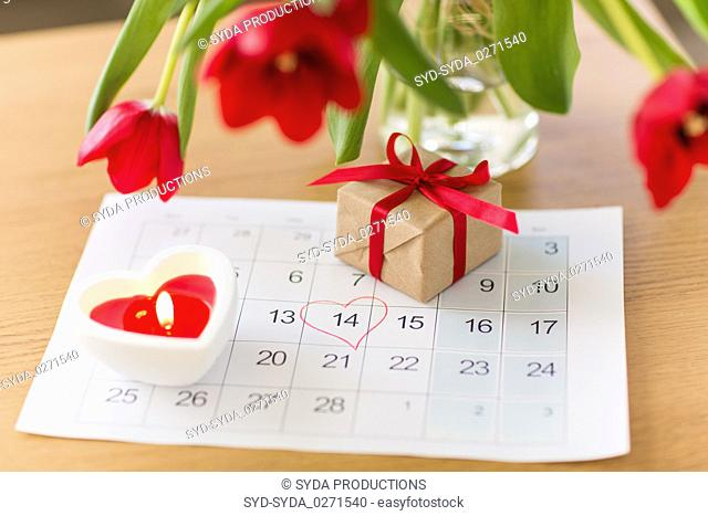 gift box, calendar sheet and flowers on table