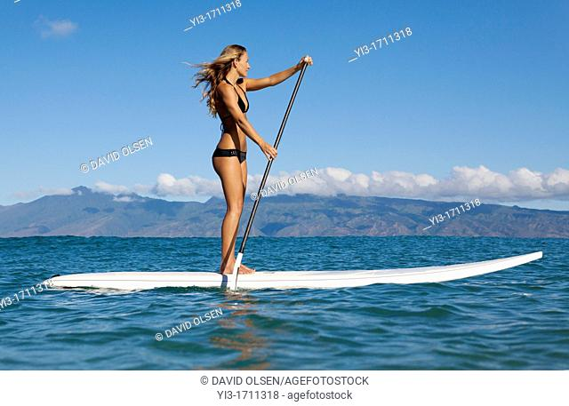 Fit, athletic woman stand up paddles at Napili Bay, Maui, Hawaii with Molokai in the distance