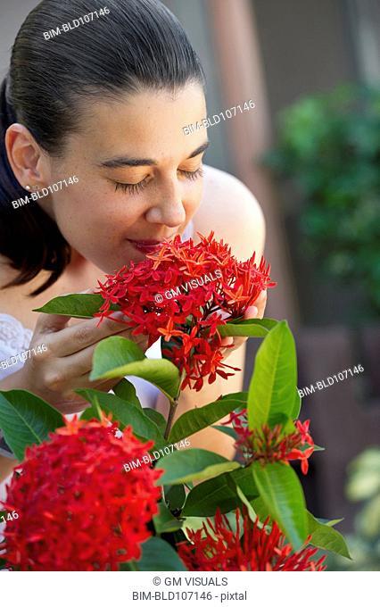 Hispanic woman smelling flowers