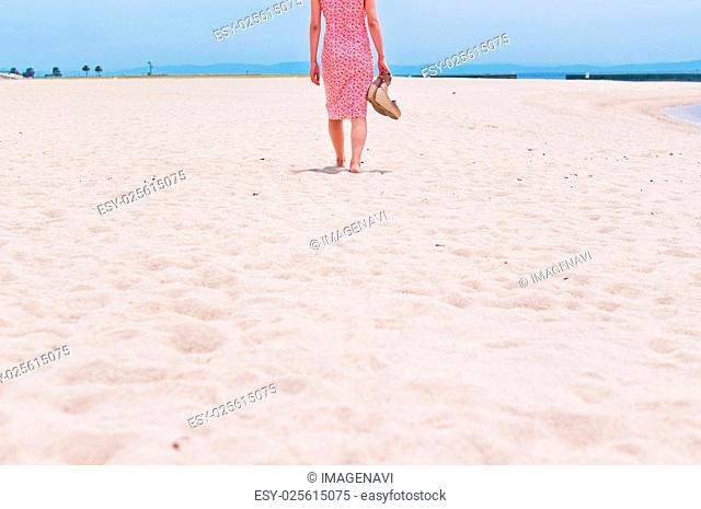 Back shot of the woman walking on the sandy beach