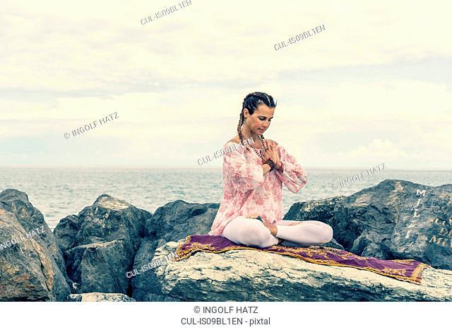 Woman meditating by sea