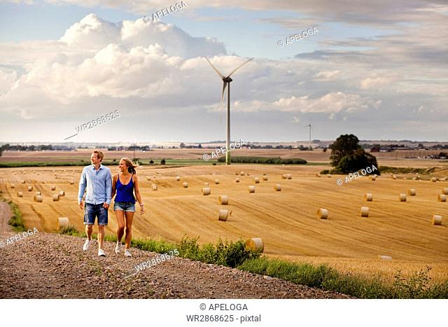 Full length of couple walking on dirt road by field against cloudy sky