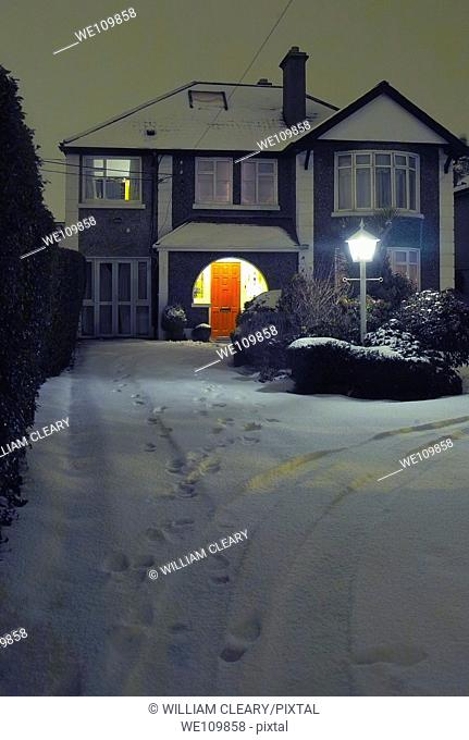The inviting red door of a house on a cold snowy December night, Clontarf, Dublin, Ireland