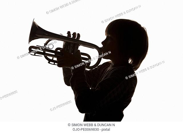 Silhouette of boy playing french horn