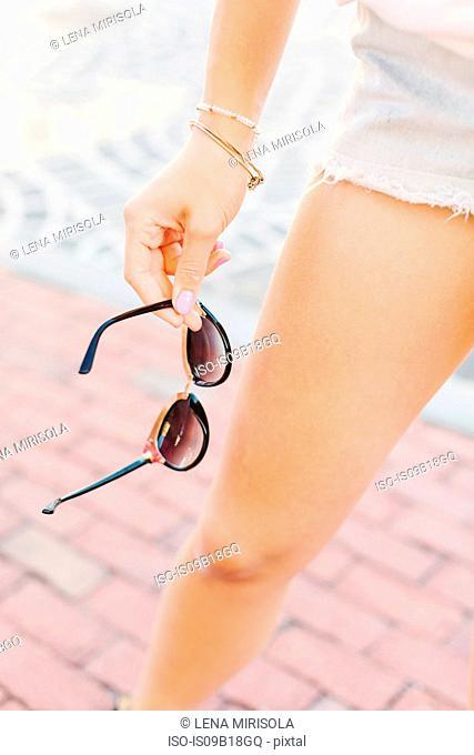 Woman holding sunglasses on street