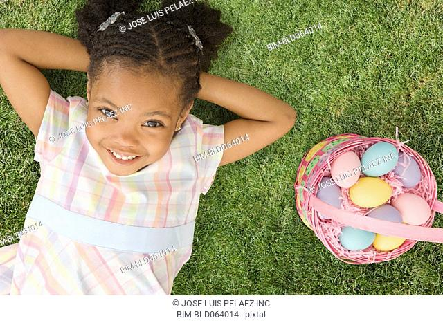 African girl laying next to Easter basket