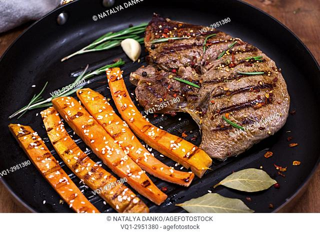 Beef stack with spices cooked with carrot sticks on a black round frying pan, close up