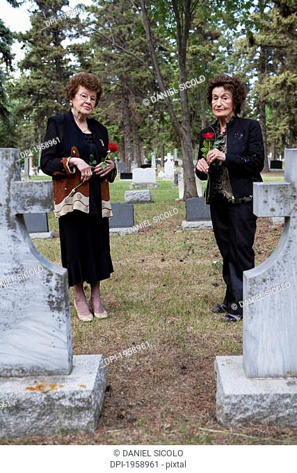Two Women Holding Single Red Roses In A Cemetery; Edmonton, Alberta, Canada