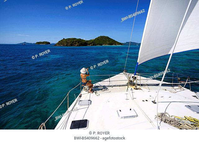 Woman taking pictures at the front part of catamaran sail boat in Tobago Cays, Saint Vincent and the Grenadines