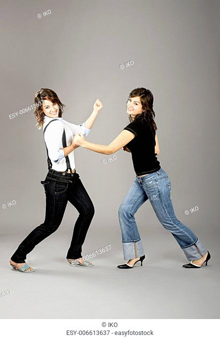 Two young beautiful sisters having fun simulating a fight - This models are true twins