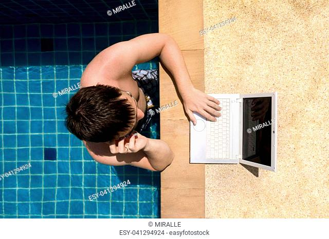 A man working with laptop and talking on the phone in the pool. Upper view