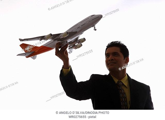 Businessman in silhouette holding passenger aeroplane in flying angle in one hand MR703T,NO PR