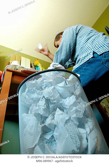 Frustrated man throws crumpled paper in trash