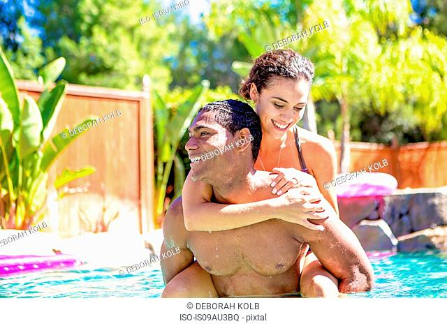 Mid adult man carrying young woman on back in swimming pool looking away smiling