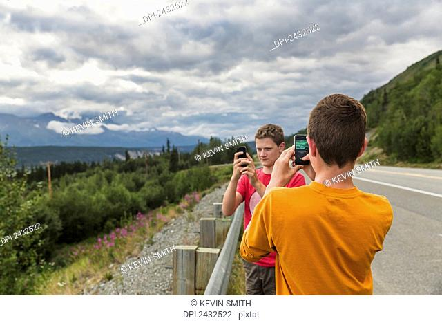 Two teenage boys on the side of the Glen highway taking photos of the Chugach mountains with cell phones; Alaska, United States of America