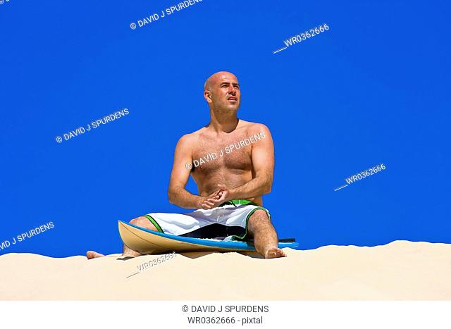 Surfer sits on surf board on beach