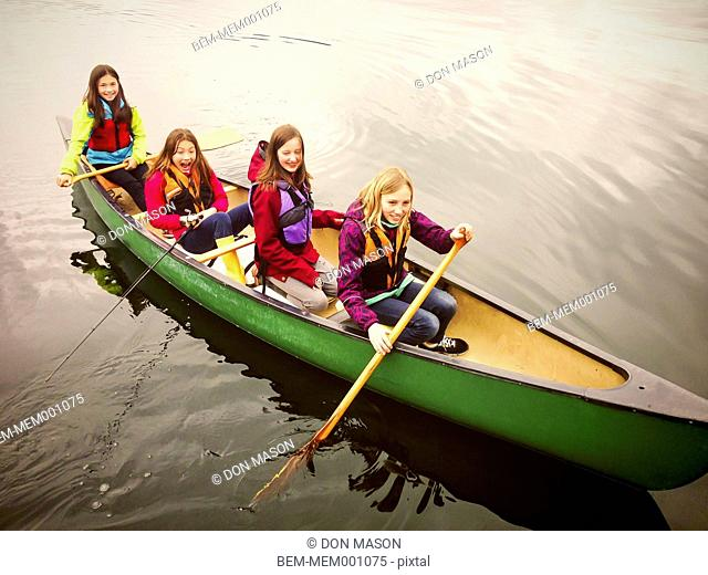 Girls rowing canoe in still rural lake
