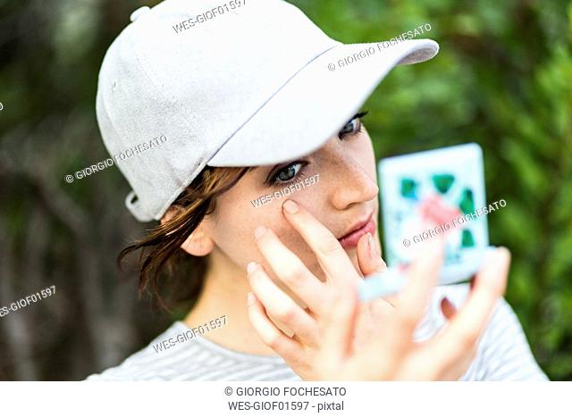 Woman using pocket mirror for checking her make up