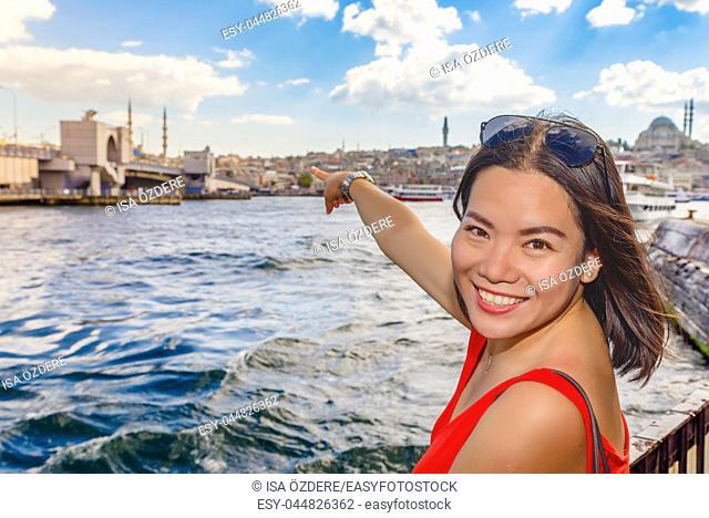 Beautiful Chinese woman shows Galata Bridge with view of Suleymaniye mosque on background