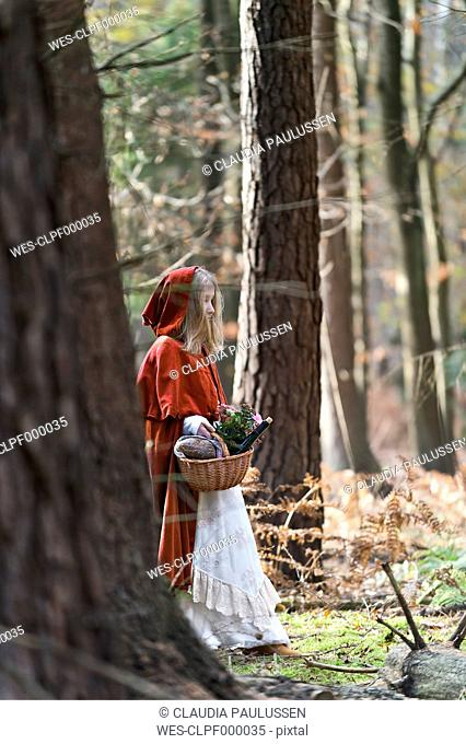 Girl masquerade as Red Riding Hood standing in the wood