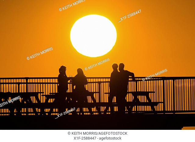 Aberystwyth Wales Uk, Tuesday 15 September 2015. . UK Weather : People in silhouette standijng on the seaside pier out enjoying the sundown in Aberystwyth Wales...