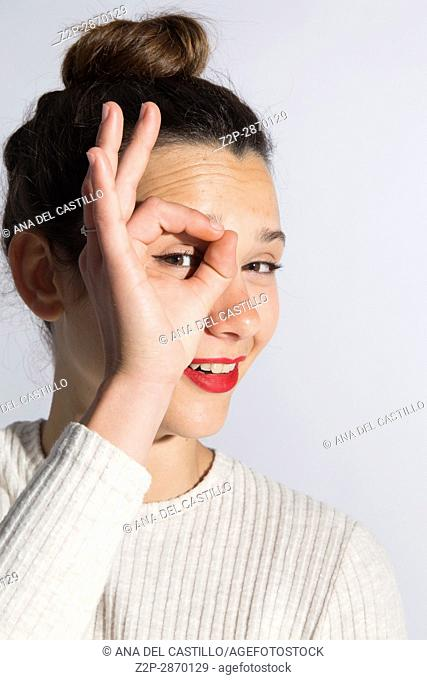 Portrait of woman looking through fingers