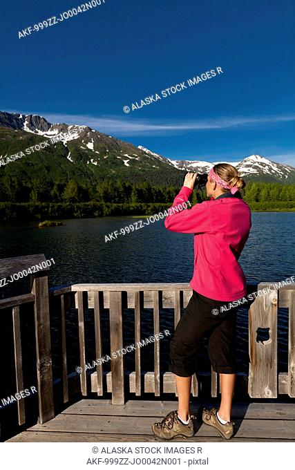 Female tourist viewing the Chugach Mountains and small pond in Portage Valley, Chugach National Forest, Southcentral Alaska, Summer