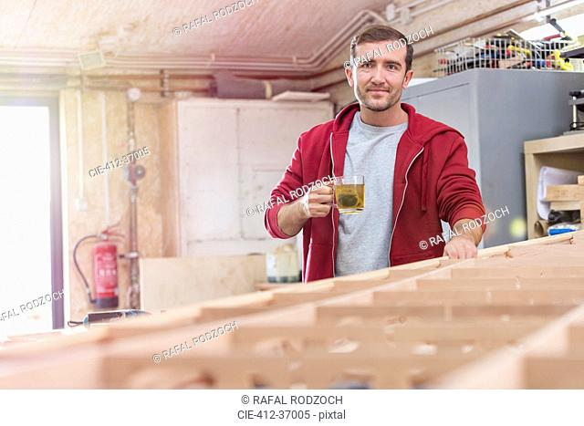 Portrait confident male carpenter drinking tea at wood boat in workshop