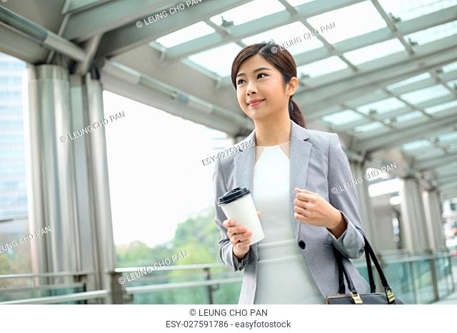 Asian Businesswoman holding a coffee and walking outdoor