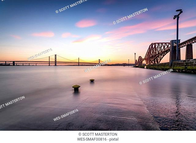 UK, Scotland, Fife, Edinburgh, Firth of Forth estuary, view from South Queensferry of Forth Bridge, Forth Road Bridge and Queensferry Crossing Bridge at sunset