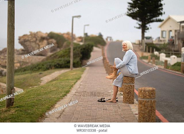 Senior woman sitting on bollard