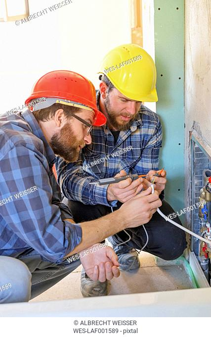 Two plumbers at work on construction site