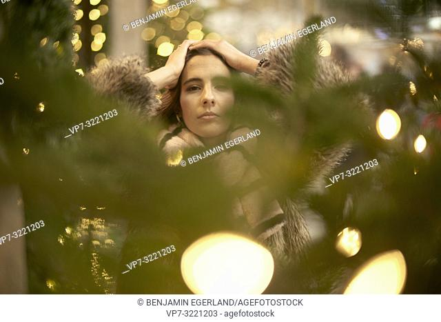 portrait of confident woman behind lights of christmas tree, in city Munich, Germany