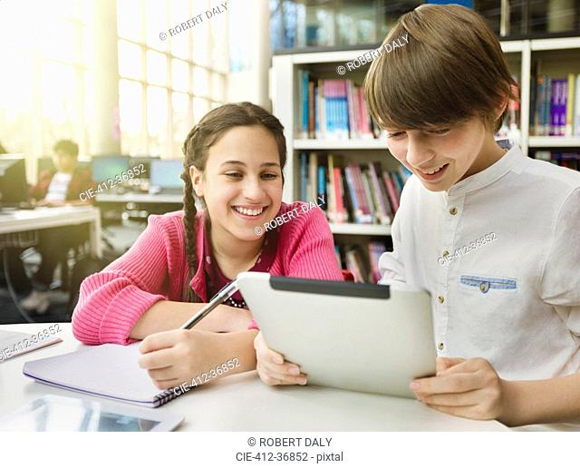 Smiling students researching, using digital tablet at table in library