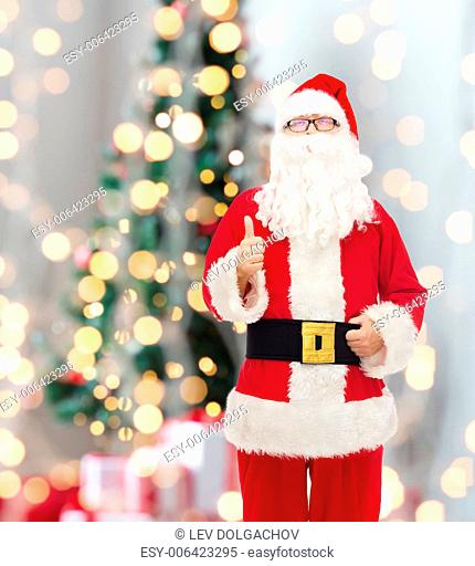christmas, holidays, gesture and people concept- man in costume of santa claus showing thumbs up over tree lights background
