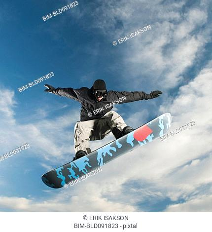 Caucasian man on snowboard in mid-air