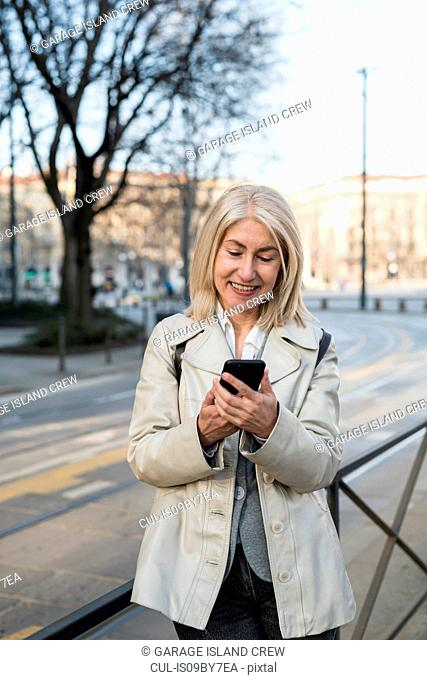 Mature woman using smartphone on sidewalk in city