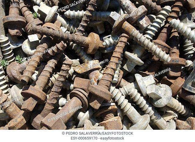 old and rusty screws on a railroad track