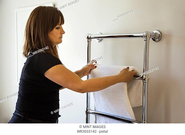 Woman standing in a bathroom, hanging fresh towel over metal towel holder