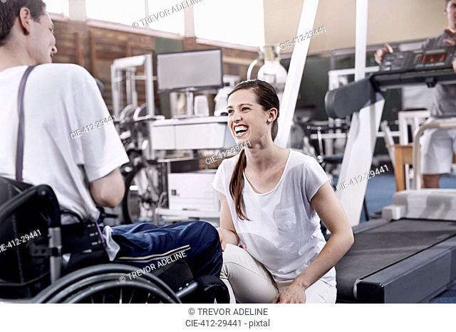 Smiling physical therapist talking to man in wheelchair